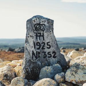 Kivipaasi, jossa tekstiä ja vuosiluku 1925, taustalla tunturimaisemaa.