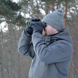 Man i grå jacka och mössa ser in i en kikare. Skog i bakgrunden.