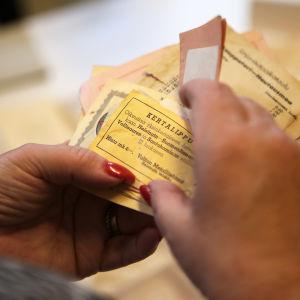 Två händer håller i en bunt med gamla biljetter, överst en gul enkelbiljett mellan Helsingfors och Sveaborg.