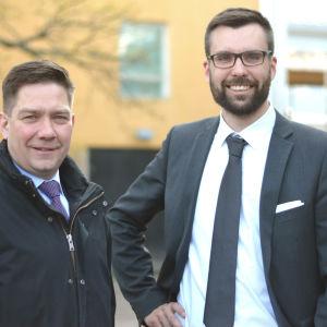 Två män i slips och kostym ler mot kameran.