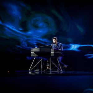duncan laurence sjunger sittandes vid ett elpiano och har ett blått skimmer runtom sig