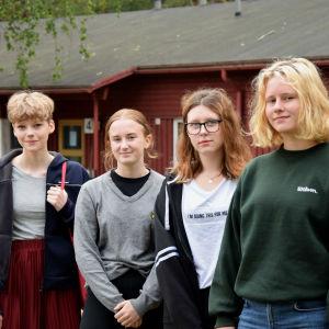 Tyra Wingren, Tyra af Kleen, Alva Runberg, Frida Hanslep-Kellen står på rad framför ett rött hus.