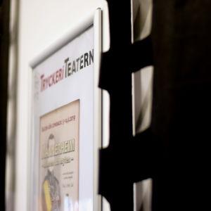 En tavla där det står Tryckeriteatern intill ett svart draperi.