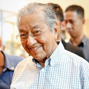 En äldre malaysisk man i rutig skjorta.