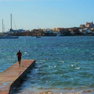 En person står på en brygga i ett blått hav. I bakgrunden Ibizas historiska centrum.