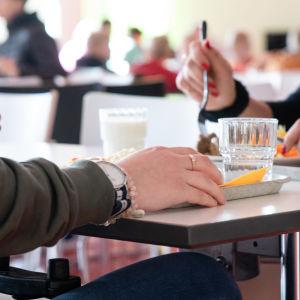 Oppilaita syömässä Kimpisen koulun ruokalassa, tarjoittimella ruokaa.