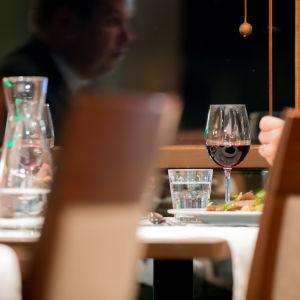 Två anonyma herrar äter middag.