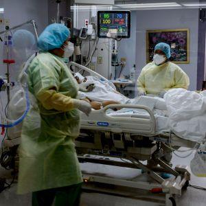 Vårdare i skyddsutrustning står vid en patients säng.