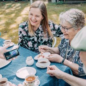 Joukko eri ikäisiä ihmisiä puutarhassa katselee Yle Areena puhelimen näytöltä.