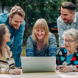Joukko eri ikäisiä ihmisiä puutarhassa kokoontuneena kannettavan tietokoneen ääreen.