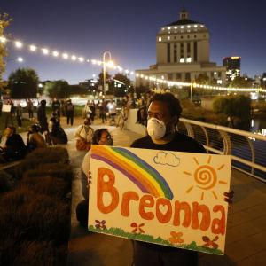 Person med ansiktsskydd bär skylt där det står Breonna.