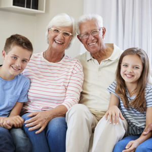 Leende äldre par med liten pojke och flicka sitter i soffa