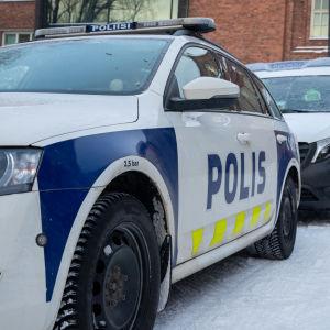 Kaksi poliisiautoa pysäköitynä peräkkäin lumisessa maisemassa oikeustalon edessä