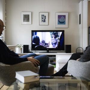 Eläkeläispariskunta katsoo Netflixiä televisiosta.