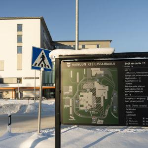 Kainuun keskussairaalan opasteviitta. Taustalla sairaalan pääovi.