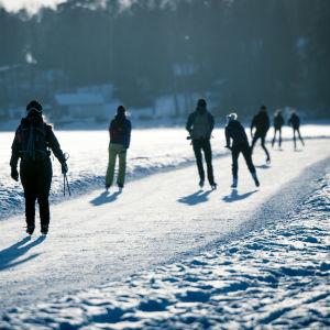 Ulkoilijoita luistelemassa meren jäällä.