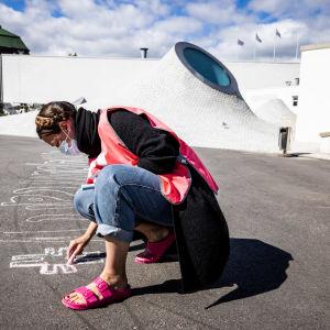 Feministisen puolueen kuntavaaliehdokkaat piirtävät iskulauseita liidulla asfalttiin.