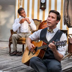 Spelamannen spelar gitarr i förgunden. Bakom honom sitter Agaton och knäpper översta knappen på sin skjorta. De är klädda i gråvita kostymkläder.