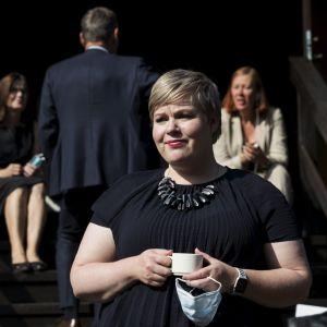 Annika Saarikko klädd i svart med en kaffekopp i handen.