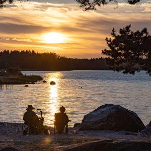 Två personer sitter på en strand under en solnedgång.