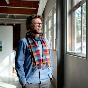 Antti står i ett soligt konstgalleri och ser ut genom fönstret. Han har en blå skjorta och röd-blå-rutig halsduk på sig.