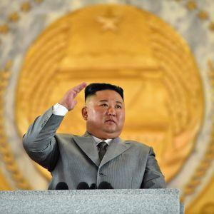 Kim Jong-un seisoo puhujanpöntön takana harmaassa puvussa ja tervehtii paraatia.