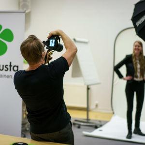 Fotograf fotograferar en av Centerns kandidater i en tillfällig fotostudio.