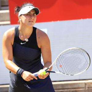 Bianca Andreescu i svart spelblus med boll och racket i handen.