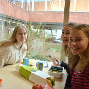 Niondeklassarna Rosa Stenbäck, Salma Krause och Ella Nihtilä sitter vid ett lunchbord.