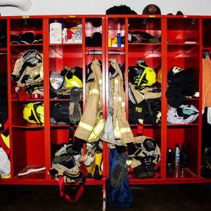 Kuvassa on palomiesten varusteita ja kypäriä.
