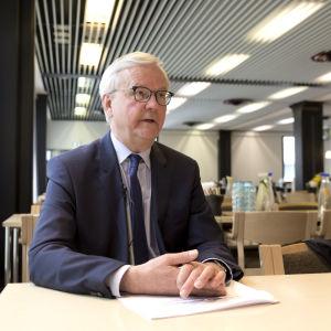 En äldre man i blå kostym sitter vid ett bord med händerna knäppta. Han ser allvarlig ut.