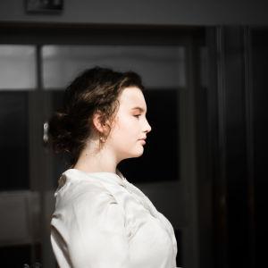En ung kvinna i en vit tröja tittar åt höger, mot en mörk bakgrund.
