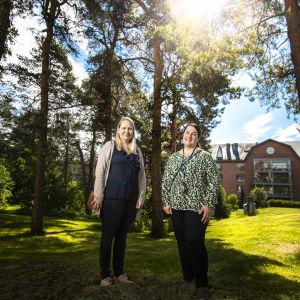 Två kvinnor, Jutta Peltoniemi och Tiia Leino, står utanför Tallbackens hälsostation en försommardag.