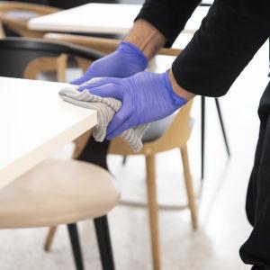 En man med gummihandskar på sig torkar av ett bord.