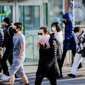 Personer med munskydd i Helsingfors centrum.