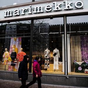 En man och en kvinna passerar Marimekkos stora skyltfönster.