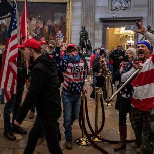 Kongressin valtaajia lippuineen pyörii ja huutaa kongressin sisällä.