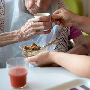 En vårdare hjälper en äldre klient att äta.