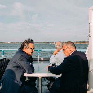Two men talking to each other over a table on the outside deck of a ferry boat.