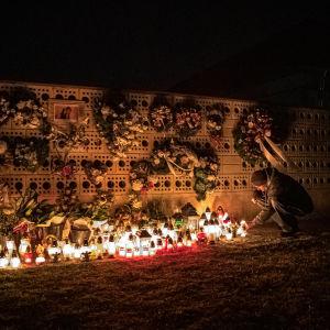Kukkakimppuja ja -seppeleitä ripustettuna tiiliseinälle, edessä kymmeniä hautakynttilöitä.