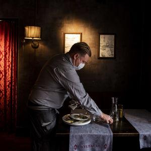 En servitör plockar ihop kärl från ett bord i en mörk restaurang.