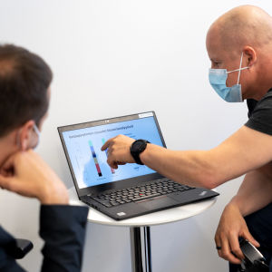 Kuvan keskellä on kannettava tietokone, jota kaksi miestä kuvan sivuilla katsoo. Oikeanpuoleinen mies osoittaa ruudulla näkyviä tilastoja ja vasemmanpuoleinen katselee.