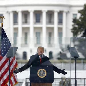 Donald Trump puhujakorokkeella Valkoinen talo taustallaan