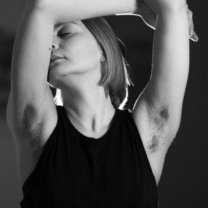 Kati Ojala ovensuussa kädet ylöspäin, kasvot puoliksi käsivarren takana.