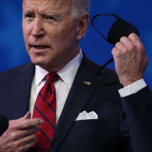 Närbild av Joe Biden som tar av sig ett svart munskydd.