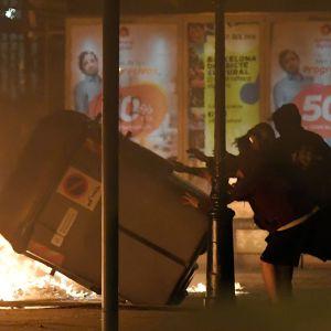Demonstranter fäller en soptunna i Barcelona. Eld i bakgrunden.