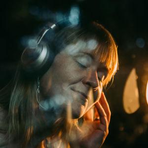 Nainen kuuntelee kuulokkeilla.