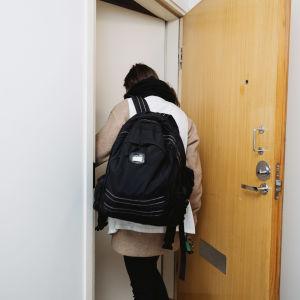 En hemvårdare stiger in i en lägenhet