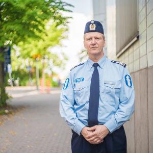 En polis står framför ett hus och ett träd. Hans min är avslappnad men allvarsam.