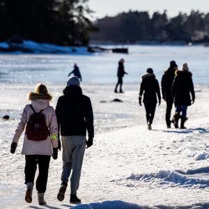 Människor som är ute och promenerar på isen vid en strand.